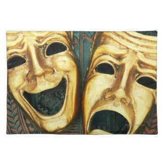 Golden comedy and tragedy masks on patterned placemat