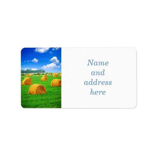 Golden hay bales in green field address label