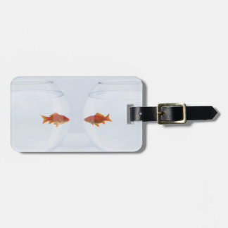 Goldfish in separate fishbowls looking face to fac luggage tag