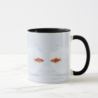 Goldfish in separate fishbowls looking face to mug