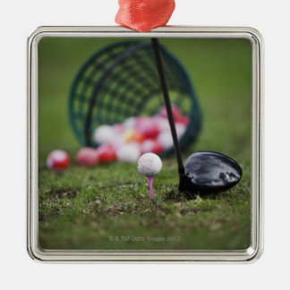 Golf ball on tee beside golf club christmas ornament