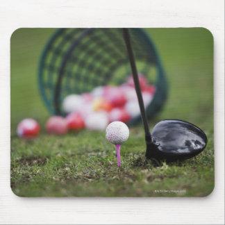 Golf ball on tee beside golf club mouse mat