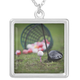 Golf ball on tee beside golf club silver plated necklace