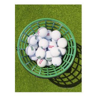 Golf balls in a basket sitting on short green postcard