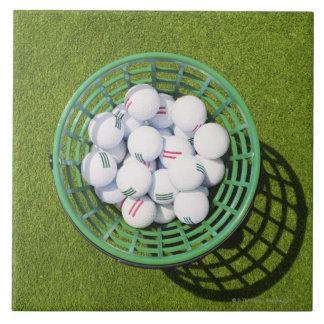 Golf balls in a basket sitting on short green tile