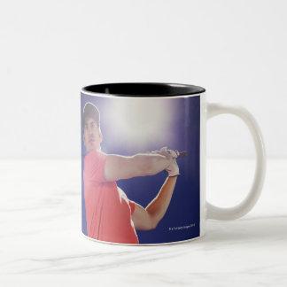 Golf player swinging club Two-Tone coffee mug