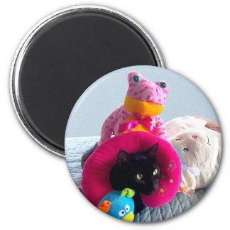 Goofy black cat hiding in stuffed toys. 6 cm round magnet