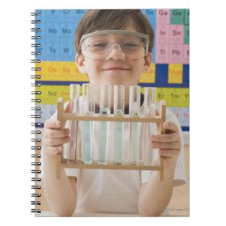 Greek boy holding rack of test tubes spiral notebook