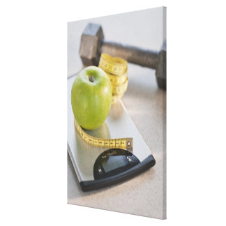 Green apple on weight scale, tape measure and canvas print