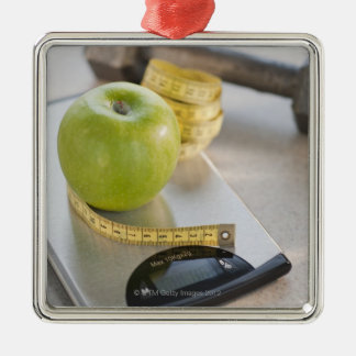 Green apple on weight scale, tape measure and christmas ornament