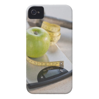 Green apple on weight scale, tape measure and iPhone 4 case