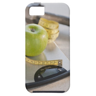 Green apple on weight scale, tape measure and iPhone 5 case