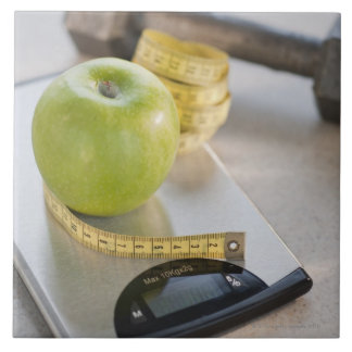 Green apple on weight scale, tape measure and tile