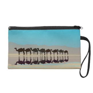 Group of camels walking in desert wristlet purses