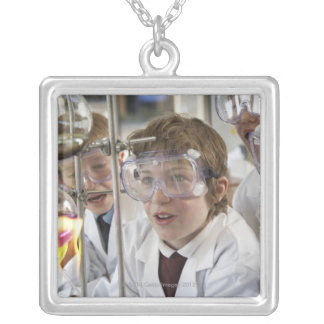 Group of children (9-12) watching experiment in silver plated necklace