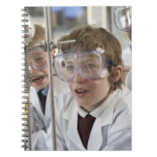 Group of children (9-12) watching experiment in spiral notebook