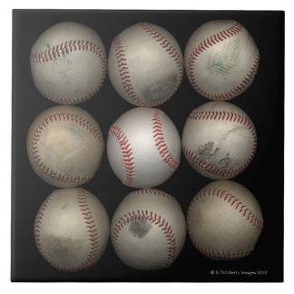 Group of old baseballs on black background tile