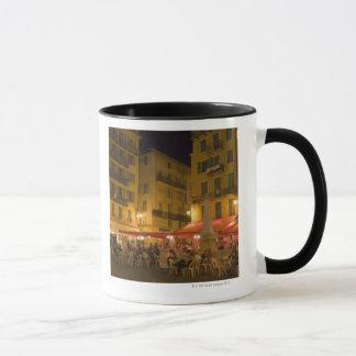 Group of people sitting at a sidewalk cafe, mug