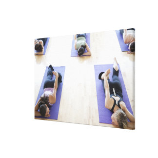 Group of woman stretching on mats in a bright, gallery wrap canvas