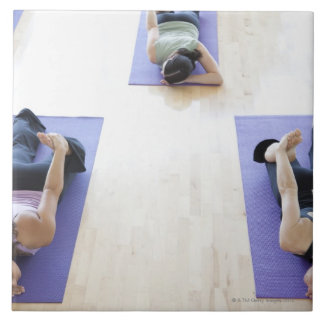 Group of woman stretching on mats in a bright, tile
