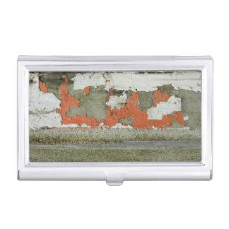 Grunge peeling orange paint on concrete wall business card holder