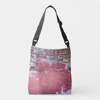 Grunge red wall with broken plaster close up crossbody bag