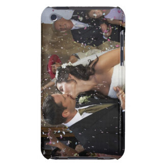 Guests throwing confetti over kissing bride and barely there iPod cases