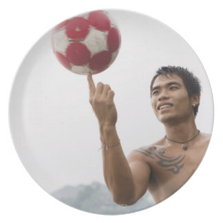 Guy spinning football on finger party plates