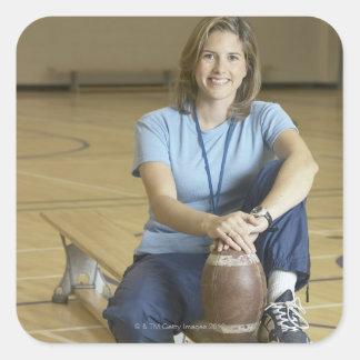 Gym teacher sitting on bench in gym square sticker