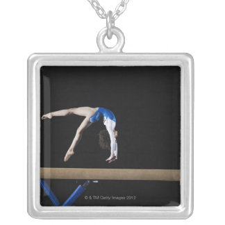 Gymnast (9-10) flipping on balance beam, side silver plated necklace