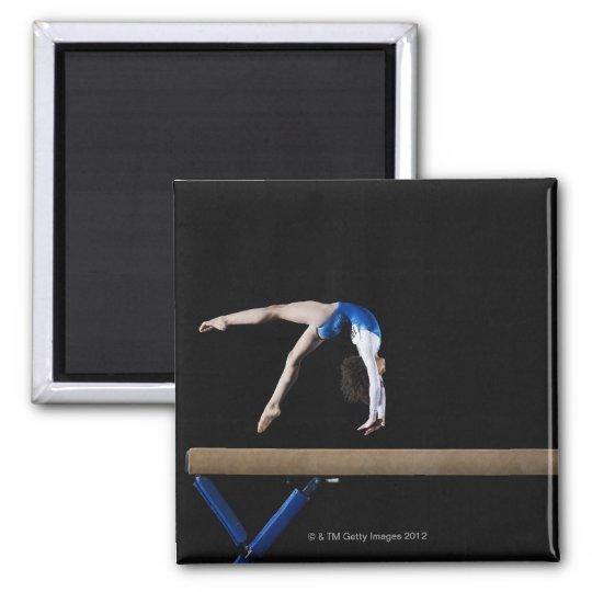 Gymnast (9-10) flipping on balance beam, side square magnet