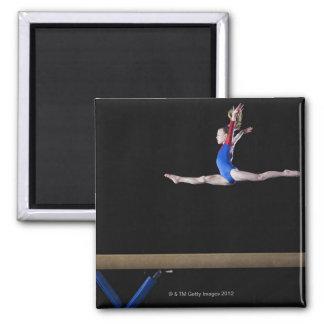 Gymnast (9-10) leaping on balance beam 2 refrigerator magnets
