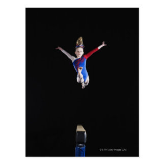 Gymnast (9-10) leaping on balance beam postcard