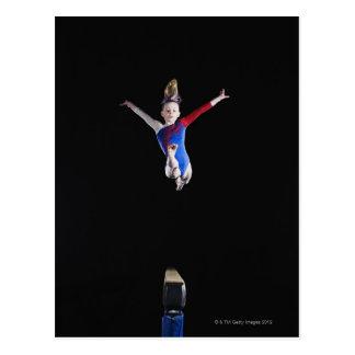Gymnast (9-10) leaping on balance beam postcard