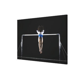 Gymnast (9-10) reaching for uneven bars canvas print