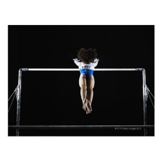 Gymnast (9-10) reaching for uneven bars postcard