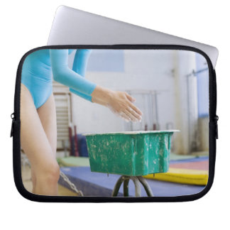 Gymnast chalking her hands laptop sleeve