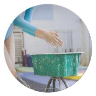 Gymnast chalking her hands plate