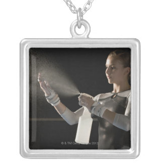 Gymnast spraying water on hands silver plated necklace
