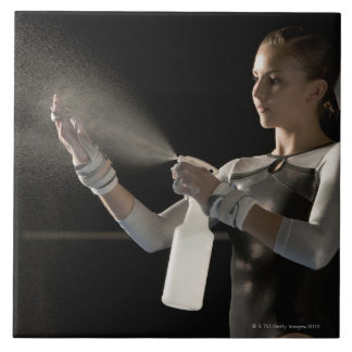 Gymnast spraying water on hands tile