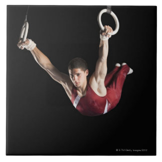 Gymnast swinging from rings tile