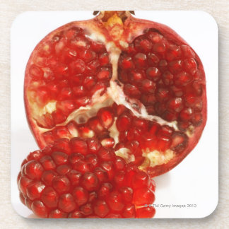 Half a ripe pomegranate cut to expose the juicy beverage coaster