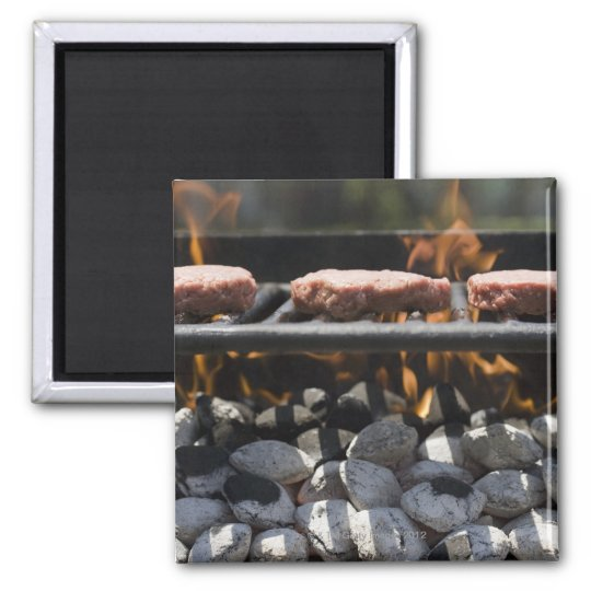 Hamburgers cooking on grill square magnet