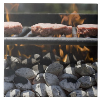 Hamburgers cooking on grill tile