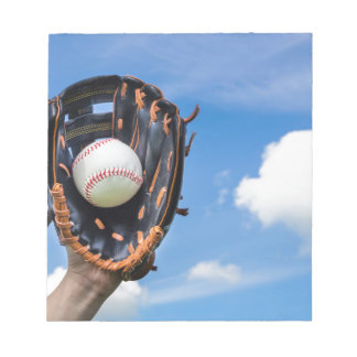 Hand holding baseball in glove with blue sky notepad