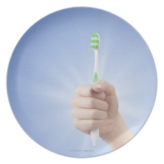 Hand holding tooth brush dinner plate