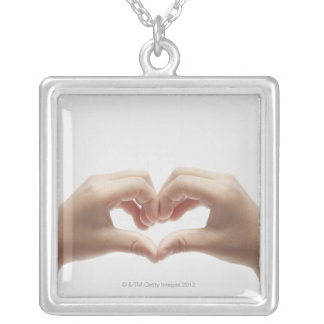 Hand of child who made shape of heart silver plated necklace