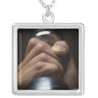 Hand of person lifting weights silver plated necklace