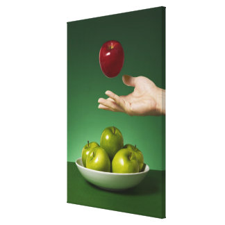 hand tossing red apple in the air and green canvas print