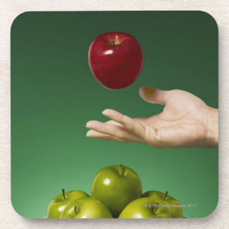 hand tossing red apple in the air and green coaster